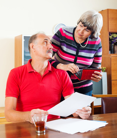 Mature couple calculating family budget at home photo
