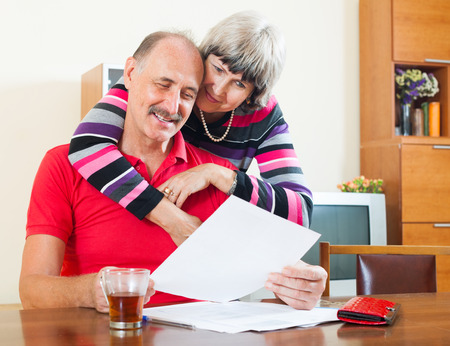 Cheeful mature man with wife reading financial documents at table photo