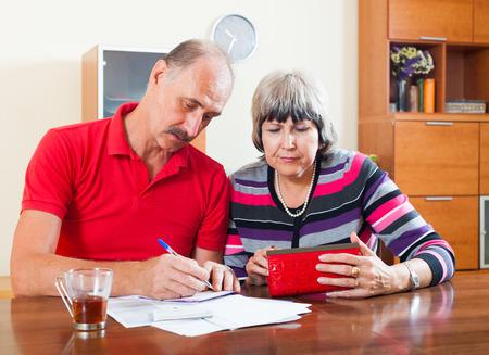 Sad senior couple calculating family budget  Stock Photo