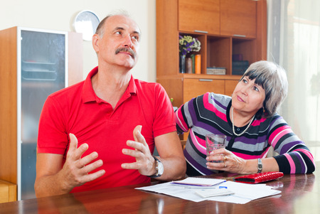 Mature man and woman having financial problems at home photo