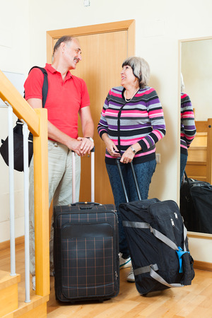 Happy mature couple with luggage   near door going on holiday photo