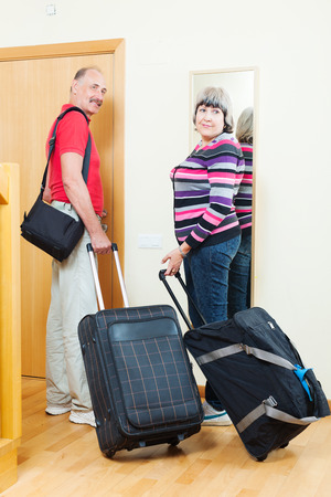 Two mature  tourists with luggage near door in home photo