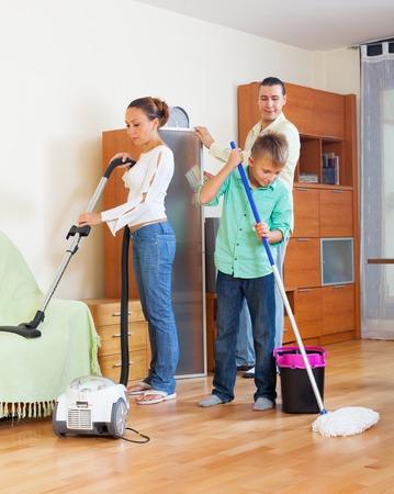 Ordinary family of three vacuuming together photo