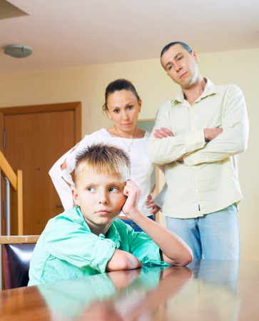 Parents scolding teenage child in home interior. Focus on boy  photo
