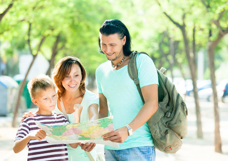 Happy family of three searching way at paper map in park photo