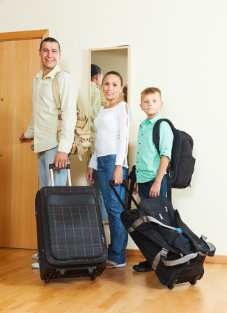 Happy family of three with luggage  going on holiday photo