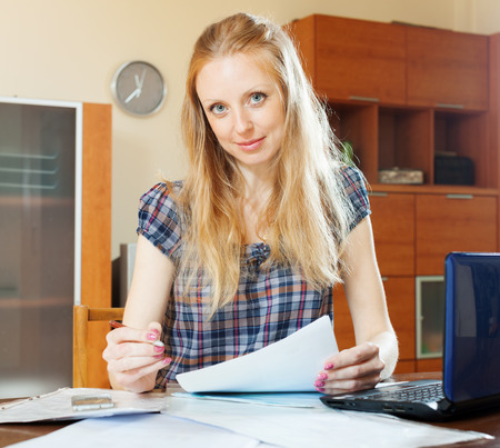 Blonde woman fills in documents at home