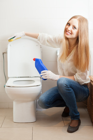 Happy long-haired woman cleaning toilet bowl with sponge photo