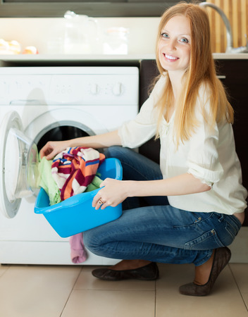 laundry room: Long-haired blonde woman using washing machine at home