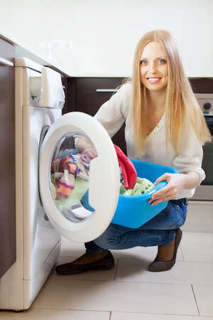Home laundry. Happy woman loading clothes into the washing machine   photo