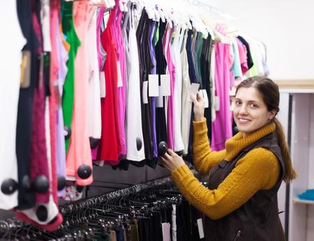 Ordinary woman choosing shirt at clothing store photo