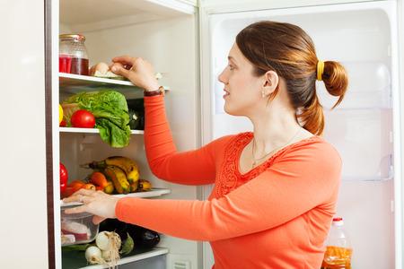 refrigerator kitchen: housewife near refrigerator  at home kitchen