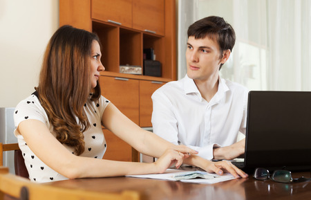Young couple calculating family budget at home interior photo