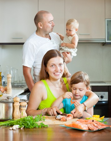 Happy and cheerful family of four fish salmon cooking at home kitchen Stock Photo - 27537911