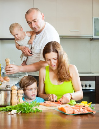 20 23 years: Happy family of four red fish salmon cooking at home kitchen