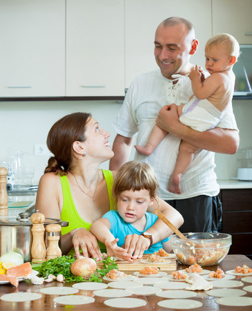 Happy family of four together in the kitchen prepares food