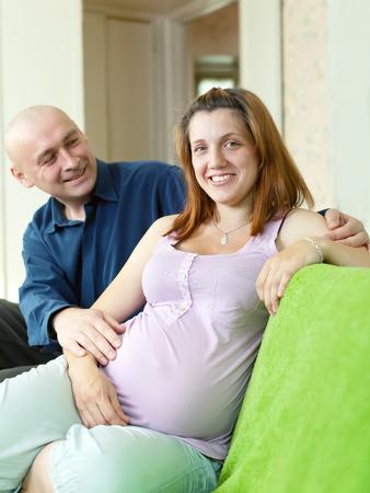 Happy pregnant couple on sofa in home interior Stock Photo - 27537835