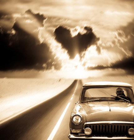 Man driving on retro car  on the road at dusk Stock Photo - 27537880