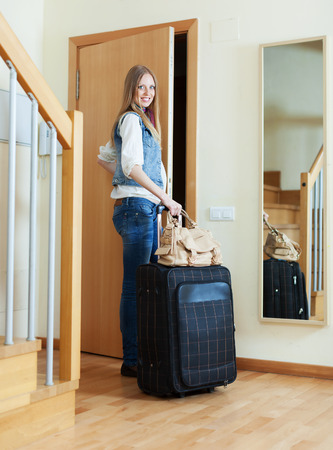 Woman with suitcase near door at home photo