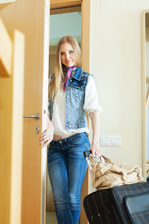Blonde positive woman with luggage leaving her home photo