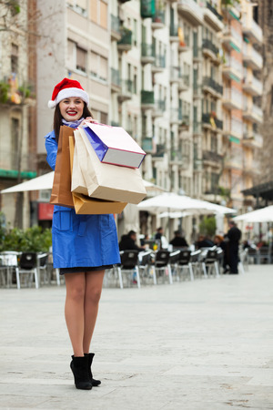 Smiling girl in coat  with purchases at street during the Christmas sales photo