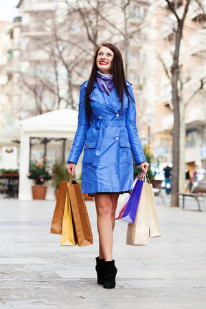 full length shot of happy woman in blue cloak with shopping bags at street  photo