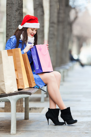 Smiling girl with shopping bags in city during the Christmas sales photo