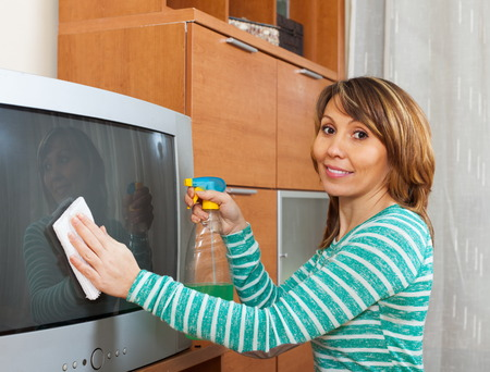 Happy housewife in green cleaning TV with rag at home photo