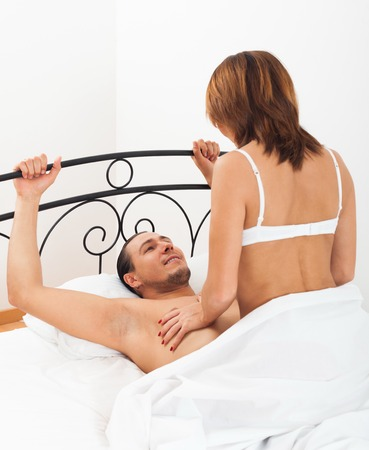 Adult man and woman having sex on bed in home interior photo