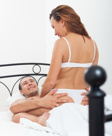 Carefree couple having sex on bed in home interior photo