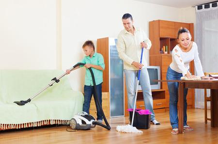 Pareja de mediana edad con el hijo adolescente que hace la limpieza de la casa en el salón de su casa Foto de archivo - 27663196