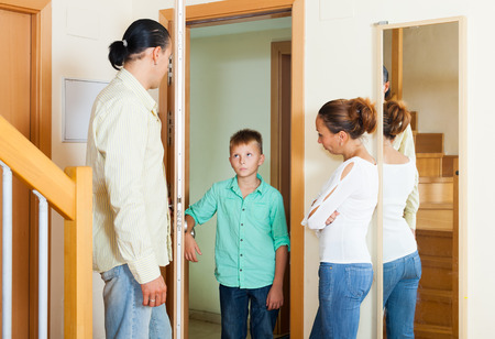 Parents meeting with scold of teenage son in the doorway at home photo