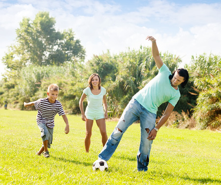 Happy family with teenager  playing with soccer ball at summer park photo