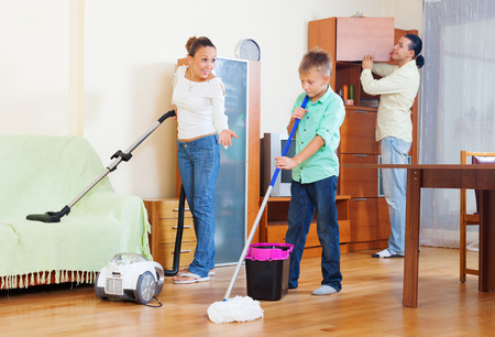 family of three with teenager doing housework with  cleaning equipment photo