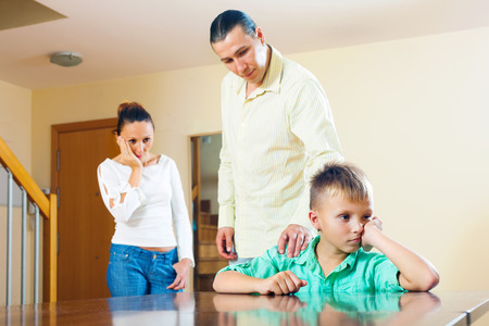 Parents scolding teenager son in home. Focus on boy only photo
