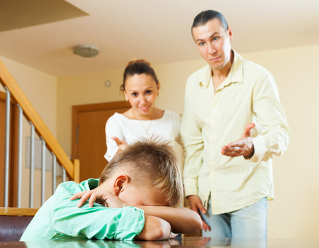 room to let: Parents scolding her teenage child in home interior. Focus on boy  Stock Photo