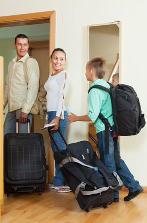 middle-aged couple and son with luggage near door in home photo