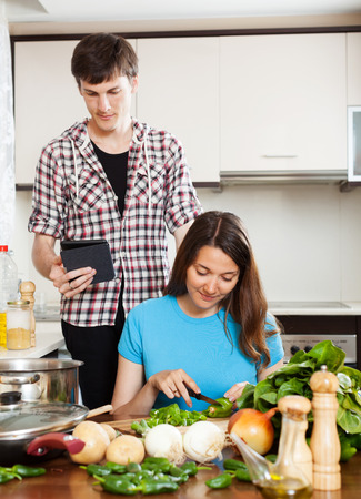 Girl preparing food while man looking at eBook in home kitchen photo