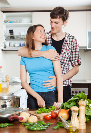 Happy young couple hugging in kitchen photo