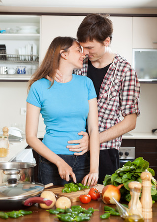 couple hugging in the kitchen while cooking photo
