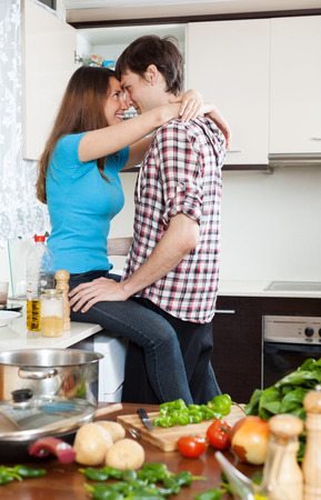 Young loving couple having sex at table in domestic kitchen photo