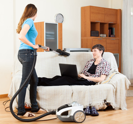 vaccuum: Girl doing sofa cleaning with vaccuum cleaner while man resting over sofa