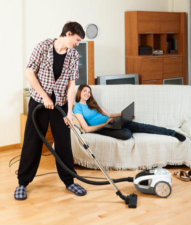 disparity: Man cleaning room during girl with notebook resting over sofa at home Stock Photo