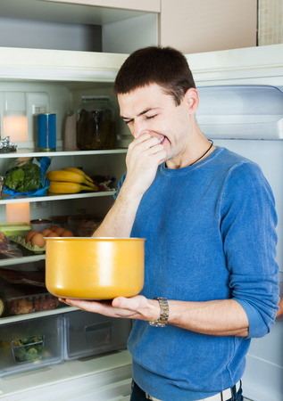 frowy: Hungry man holding his nose because of bad smell from food near refrigerator at home