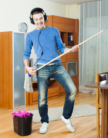 Cheerful man  cleaning with mop in living room photo