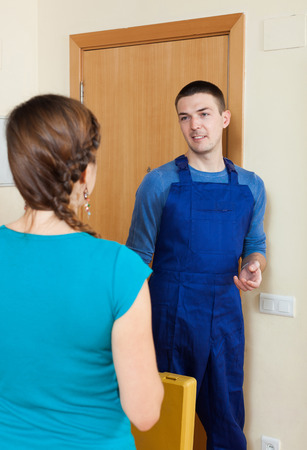 Young woman  meeting service worker at the door at home photo