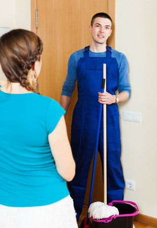 houseman: Girl meeting handsome cleaner at the door at home Stock Photo