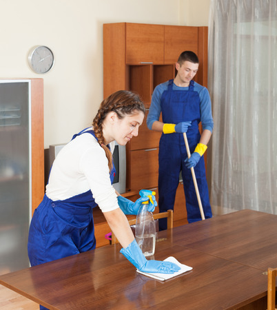 company premises: Team of professional cleaners cleaning in room at home
