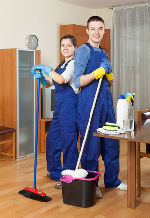 company premises: Smiling cleaners team working at living room