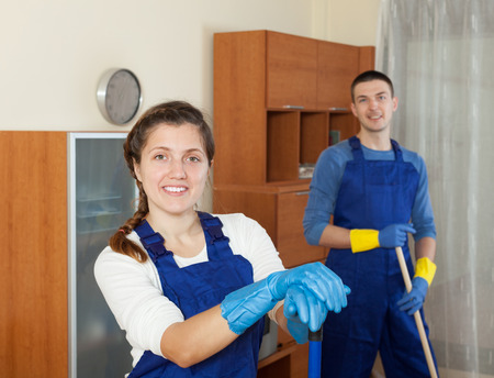 Professional cleaners in uniform cleaning in room photo